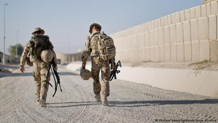 Soldados da Otan andam de costas em rua sem asfalto