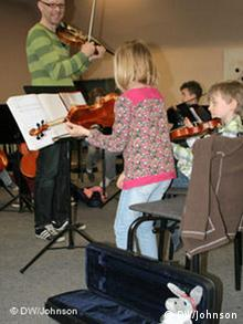 Young violinist practicing with the violinos. Her toy donkey in violin case listens in.