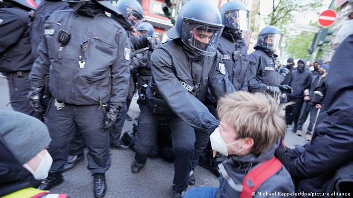 A person surrounded by police in riot gear in Berlin