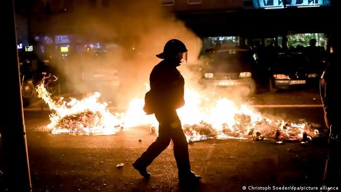 Policial anda em frente a objetos pegando fogo em rua de Berlim