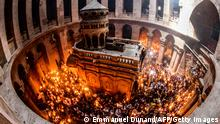 01.05.2021 TOPSHOT - Orthodox Christians gather with lit candles around the Edicule, traditionally believed to be the burial site of Jesus Christ, during the Holy Fire ceremony at Jerusalem's Holy Sepulchre church, on May 1, 2021. (Photo by Emmanuel DUNAND / AFP) (Photo by EMMANUEL DUNAND/AFP via Getty Images)