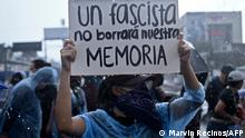 """A demonstrator holds a sign reading """"A fascist will not erase our memory"""" during a protest against the latest measures taken by the Legislative Assembly, including the dismissal of the Supreme Court judges and the Attorney General, in San Salvador, on May 2, 2021. - A political storm has erupted in El Salvador as its parliament, newly controlled by President Nayib Bukele's party, dismissed the attorney general and top judges deemed hostile to the populist leader. (Photo by Marvin Recinos / AFP)"""