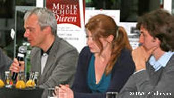 Three music teachers, one with microphone, at podium discussion in Dueren.