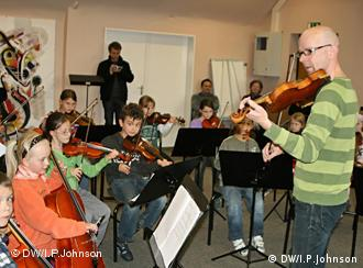 Duisburg's junior string ensemble, the violinos, with music teacher Joachim Schaeffer