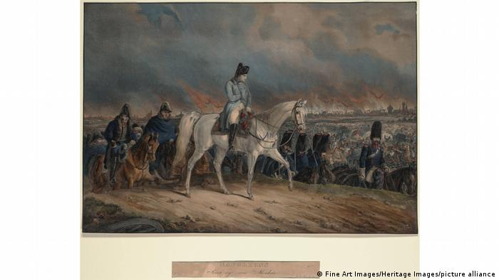 Napoleon on a white horse leading troops out of a city in flames.