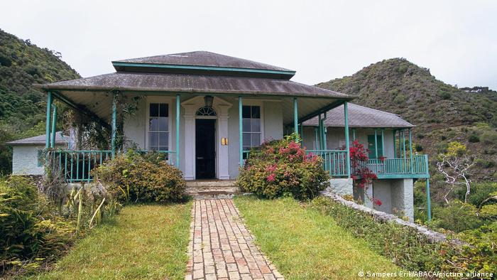 A house with a light blue veranda back-dropped by hills.