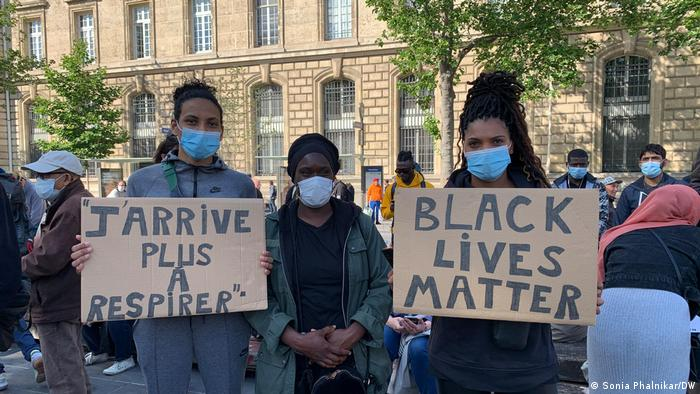 Two people holding placards during a demonstration following the killing of George Floyd in the US, one says I can't breathe in French and the other reads Black Lives Matter