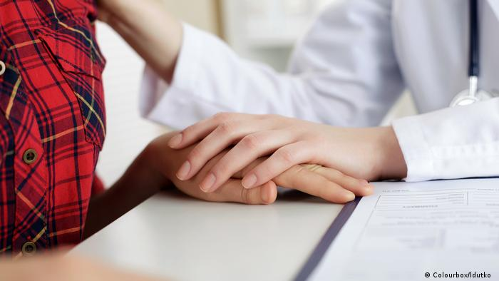 A female doctor comforting a female patient (close-up of theirs hands)