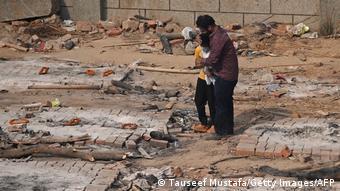Мужчина с сыном на месте кремации в Нью-Дели