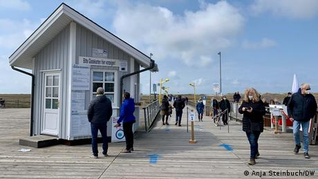 Germany, people wearing face masks on a pier in North Fresia