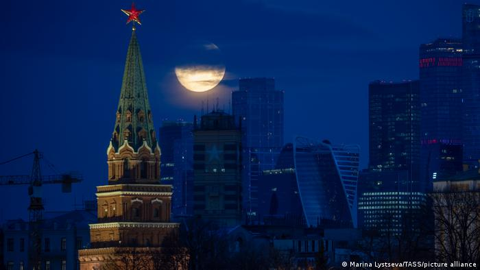 A full moon shines over the Moscow Kremlin and the Moscow International Business Center.