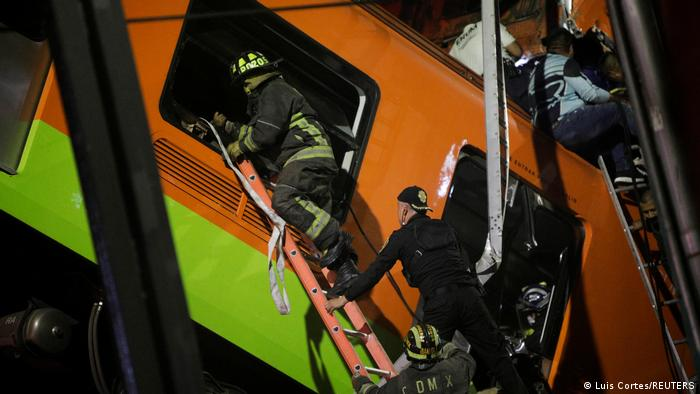 Rescue workers climbing a ladder into the handing metro train carriage