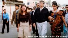 FILE - In this Dec. 5, 2005, file photo, Bill Gates, founder and chairman of Microsoft Corp., center, and his wife Melinda, left, walk on a street in Dhaka, Bangladesh. The couple announced Monday, May 3, 2021, that they are divorcing. The Microsoft co-founder and his wife, with whom he launched the world's largest charitable foundation, said they would continue to work together at The Bill