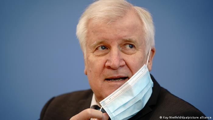 Horst Seehofer removes a face mask