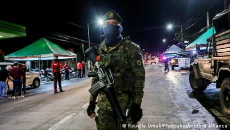 Nighttime, armed and masked soldier in Valenzuela City looks into the camera