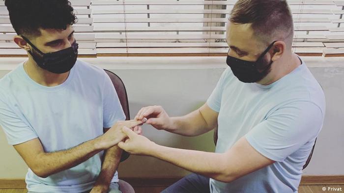 Homens de máscaras de proteção trocam alianças