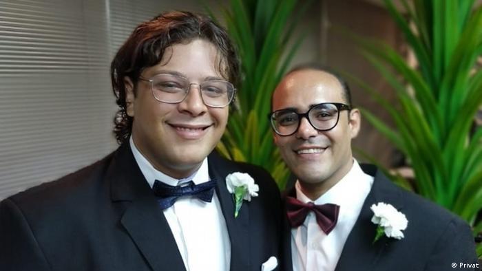 Casal de homens veste terno e gravata borboleta