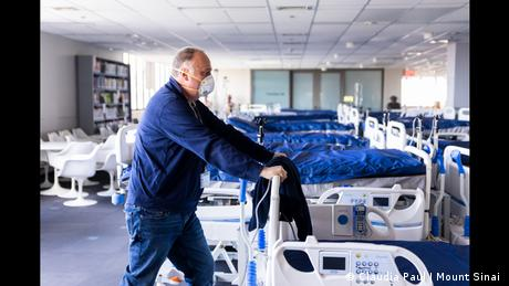 A man in blue overalls pushing a hospital bed.