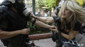 A riot policeman pushes away a protester who was trying to stop officers detain a suspected rioter during clashes at a union protest in Athens on Tuesday, June 29, 2010. Some 16,000 people took part in two separate demonstrations, the second of which turned violent as stone-throwing youths fought with riot police. Public services shut down across Greece Tuesday as workers walked off the job in a new nationwide general strike that disrupted public transport left hospitals operating on emergency staff and pulled all news broadcasts off the air. (AP Photo/Petros Giannakouris)