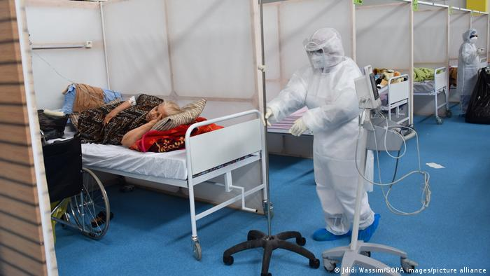 Hospital scene, masked person in white protective suit approaches a bed with a patient, more beds lined up in the background