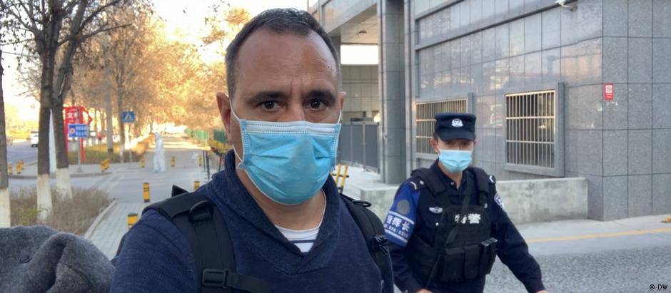 Mathias Bölinger in Beijing, man wearing face mask looks into camera, policeman in the background