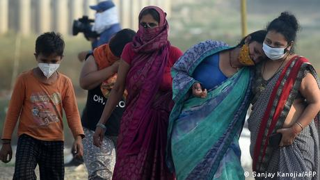 Relatives mourn during the cremation of their loved one who died due to COVID in Allahabad