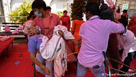 A family member carries a COVID-19 patient in Ghaziabad