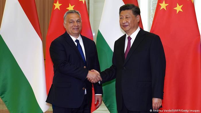Viktor Orbán und Xi Jinping schütteln sich vor den Flaggen Ungarns und Chinas die Hände