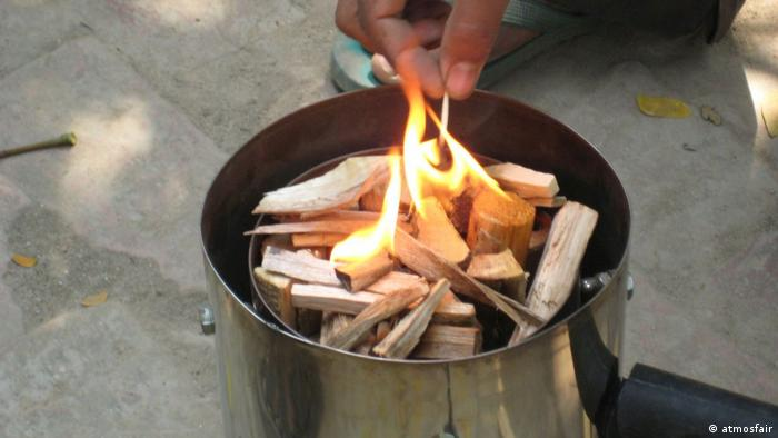 A person lights a fire in a fuel-efficient cook stove in India