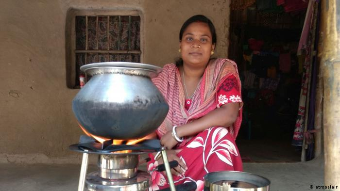 A woman sits next to a fuel-efficient cook stove in India