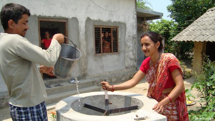 A man pours water into a biogas digester in Nepal, while a woman in a red sari looks on