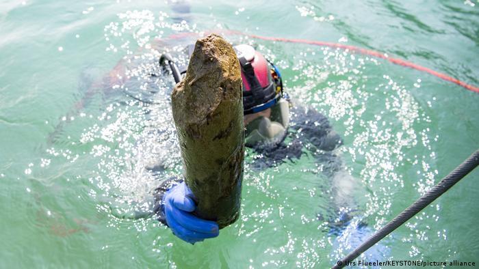 Un buceador sale con un trozo de madera recuperado del lecho fangoso del lago de Lucerna.