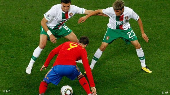 Spain's Fernando Torres, bottom, faces Portugal's Pepe, left, and Fabio Coentrao