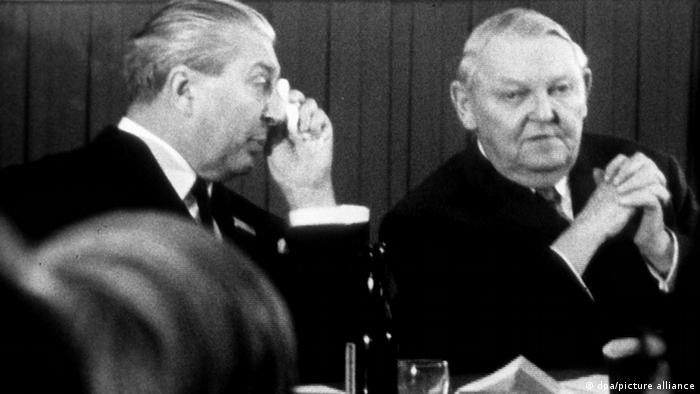Kiesinger seated next to a colleague with his hands folded in front of his chest.