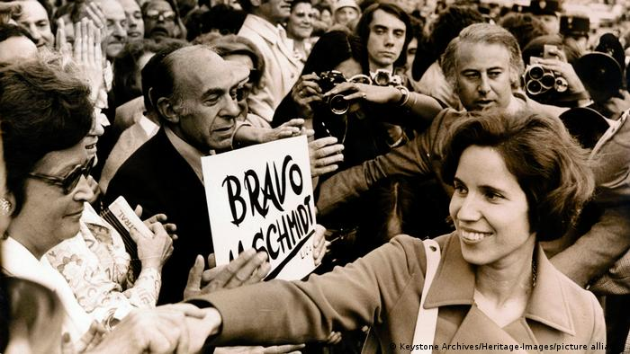 Beate Klarsfeld shakes the hands of fans with one holding up a sign saying bravo.