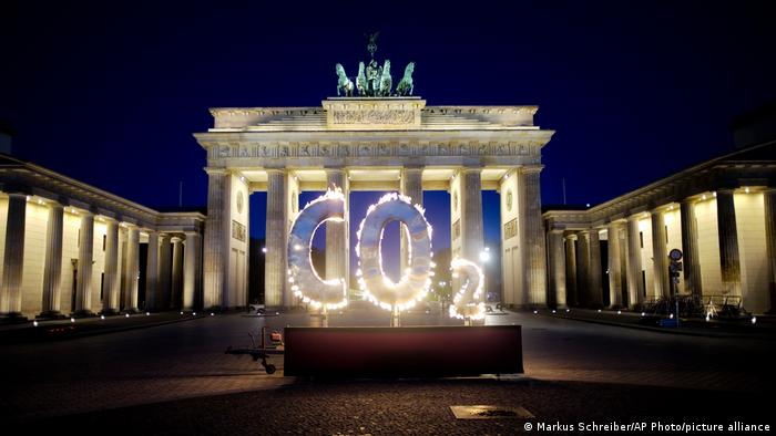 The letters CO2 illuminated in flames in front of the Brandenburg Gat ein Berlin