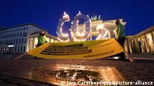 Greenpeace-Aktivisten mit brennenden CO2-Buchstaben und einem Protestbanner vor dem Brandenburger Tor