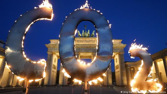 Letreiro CO2 em chamas, com Portão de Brandemburgo ao fundo