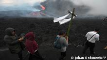 A woman carries a wooden cross as residents make a pilgrimage to the Pacaya volcano to call for the cessation of activity at the volcano in Cerro Chino, San Vicente Pacaya municipality, south of Guatemala City, on May 5, 2021. - A new fissure vent opened recently in the Pacaya volcano which has maintained high levels of activity with strong eruptions, ash clouds and rivers of lava spewing out. The 2,500-metre (8,200-foot) volcano has been erupting for weeks, damaging plantations in the path of the lava and threatening nearby communities. (Photo by Johan ORDONEZ / AFP)
