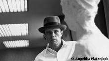 Joseph Beuys steht neben einer Skulptur
