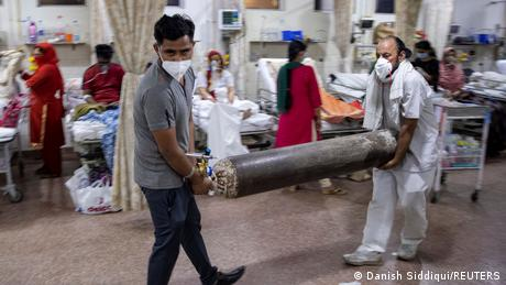 Men carry an oxygen cylinder in the emergency room of Holy Family Hospital in New Delhi, India
