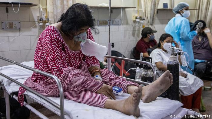 Woman suffering from COVID-19 sits on a bed inside the emergency room of Holy Family Hospital in New Delhi