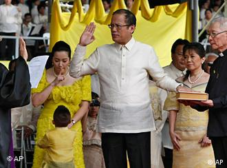 President Benigno Aquino III, center, takes his oath before Supreme Court Associated Justice Conchita Carpio-Morales as the Philippines' 15th President during inaugural ceremony Wednesday June 30, 2010 in Manila, Philippines. Aquino, the only son of Philippine democracy icons, the late President Corazon Aquino and assassinated opposition leader Sen. Benigno Aquino Jr., won by a landslide in the May 10 automated presidential elections. At right holding the Holy Bible is Jesuit priest Father Catalino Arevalo. (AP Photo/Bullit Marquez)
