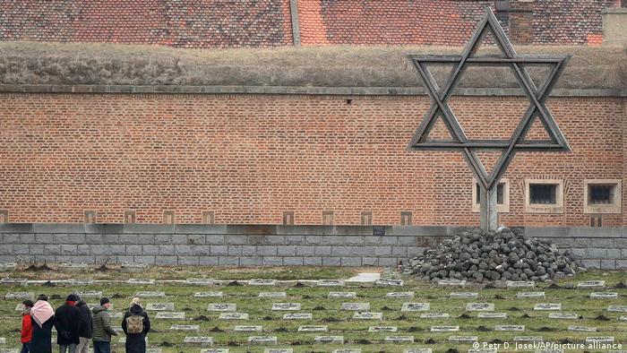 Wiesenfläche mit Grabsteinen, ein großer Judenstern ist an dessen Ende zu sehen.