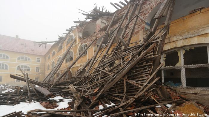 Holzbalken einer eingestürzten Kaserne sind in den Innenhof gekracht.