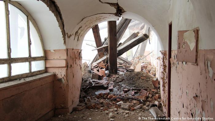Dachgebälk ist in einen Gang gestürzt, die Mauern haben starke Risse, die Farbe blättert von den Wänden ab.