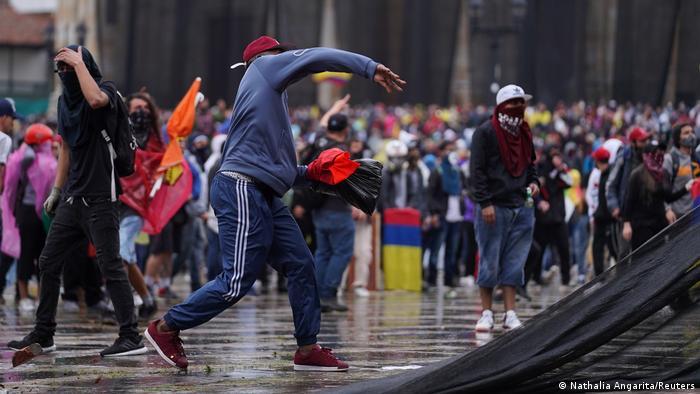 Un manifestante tira piedras a la policía en Colombia.