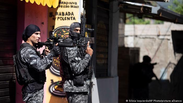 Dois policias com fuzis tomam posição em rua de favela carioca. Ação policial contra traficantes na favela do Jacarezinho, na zona norte do Rio, deixou ao menos 25 mortos. STF julgará decisão que impôs limites a operações desse tipo durante a pandemia. Polícia Civil do Rio de Janeiro afirma que agiu dentro da lei e critica o que chama de ativismo judicial, que resultaria no fortalecimento do tráfico no estado. (06/05)