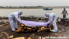 Workers in protective suits prepare the cremation of someone who died from coronavirus, on the banks of the river Ganges