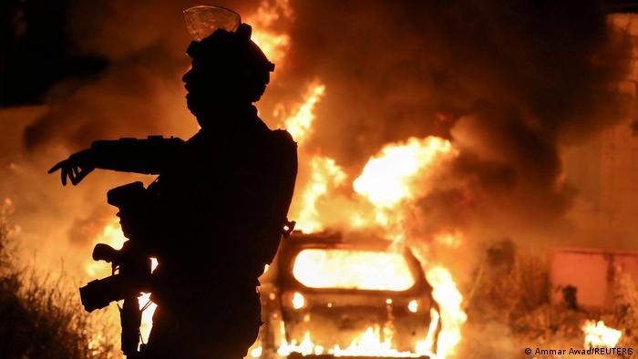 Silhueta de policial diante de carro em chamas